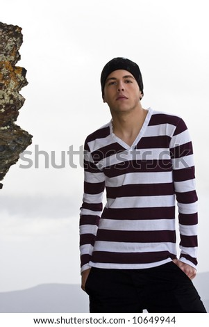 Young man portrait in casual clothing on the rocks. Subject can be isolated too. - stock photo