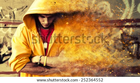 Young man portrait in hooded sweatshirt, jumper on grunge graffiti wall. Particles effect - stock photo