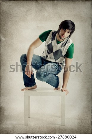Young man portrait seated over a grunge background - stock photo
