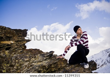 Young man posing at high altitude after climbing a cliff - stock photo