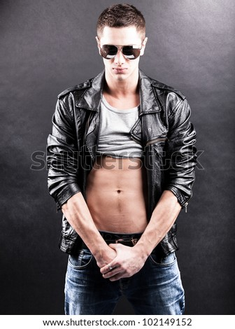 Young man posing in black leather coat - stock photo