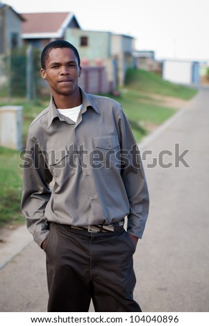 Young man posing in the street of shack town. - stock photo