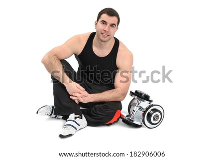 young man posing with dumbbell sitting on floor, on white background