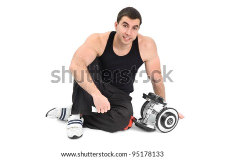 young man posing with dumbbells sitting on floor, on white background