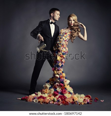 Young man pours from watering can a beautiful lady in flower dress - stock photo