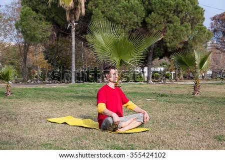 Young man practicing yoga and meditating. - stock photo