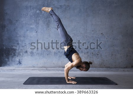 Young man practicing yoga in a urban background - stock photo