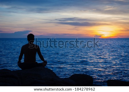 Young man practicing yoga on ocean shore at sunset
