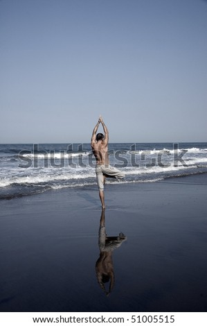 young man practicing yoga on the beach, Goa, India.