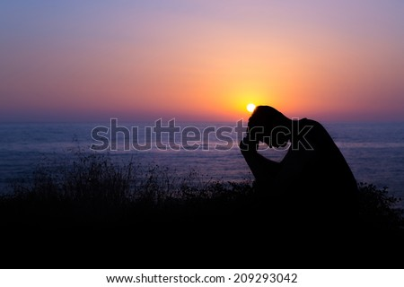 Young man praying to God during sunset by the sea - stock photo
