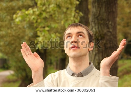 young man prays outdoor in summer - stock photo