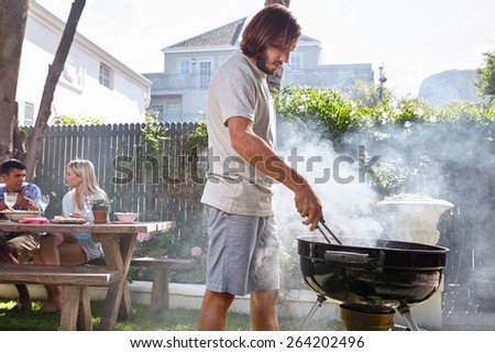 young man preparing fire for friends outdoor barbecue garden party - stock photo