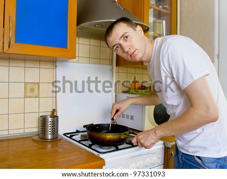 Young man preparing food in the kitchen - stock photo