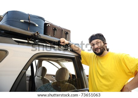 Young man preparing for trip, baggage on car roof - stock photo