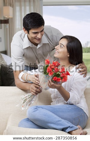 Young man presenting flowers to beautiful woman