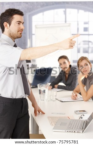 Young man presenting in meeting room, pointing, audience listening.? - stock photo