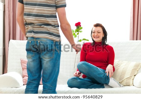 Young man presenting red rose to her girlfriend