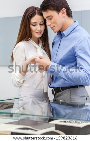 Young man presents engagement ring to his girl at jeweler's shop. Concept of wealth and luxurious life - stock photo