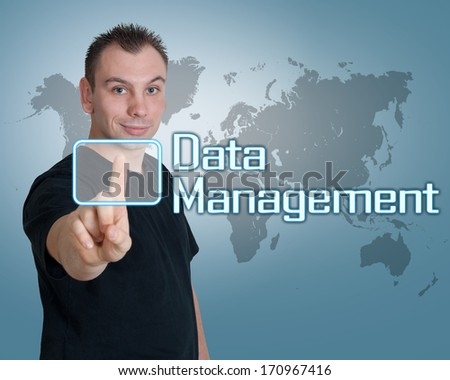 Young man press digital Data Management button on interface in front of him - stock photo