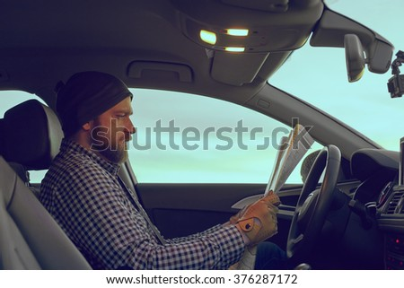 Young Man Professional Driver Looking In To The Paper Map Inside Luxury Car  With Leather Interior