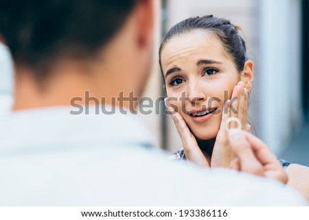 Young man proposing to girlfriend holding engagement ring - stock photo