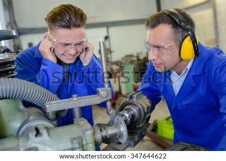 Young man protecting ears from noisy machinery - stock photo