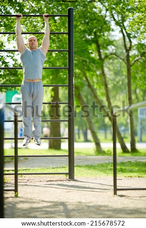 Young man pulling up on sport equipment outside - stock photo