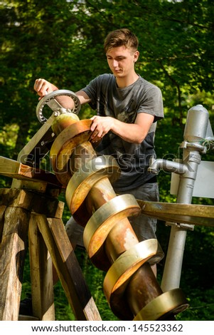 Young man pumping water with spiral pump (Archimedean pump).