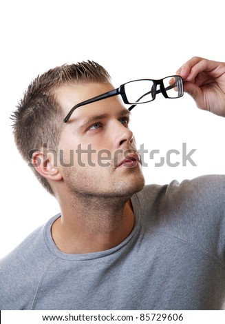 Young man puts his glasses on - stock photo