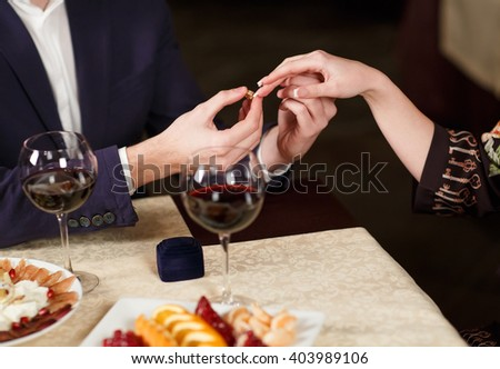 Young Man puts the ring on the finger of his girlfriend. - stock photo