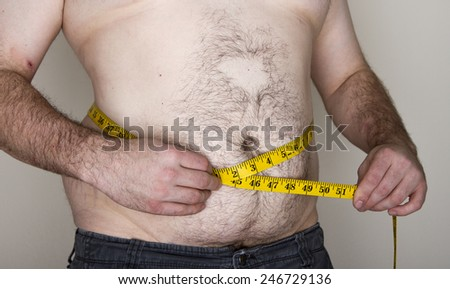 Young man putting a measuring tap against his abdomen trying to see how large he is - stock photo