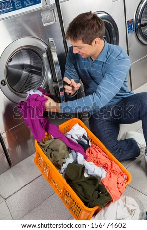 Young man putting clothes in washing machine at laundry