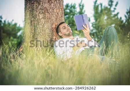 Young man read book and repose in grass. Guy leaning against a tree relaxing - resting - stock photo