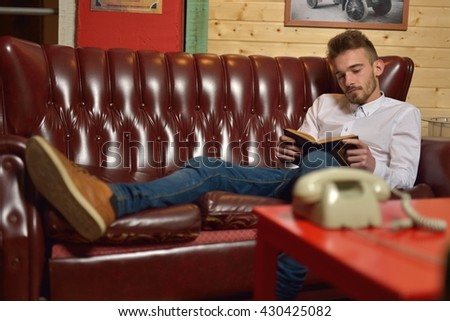 young man reading a book in vintage style sofa