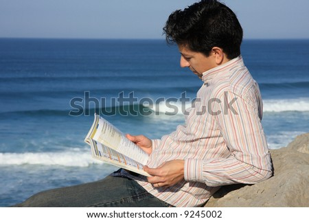 Young man reading a book on a rock with a great view over the sea - stock photo