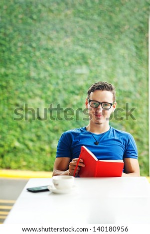 Young man reading a red book at home - stock photo
