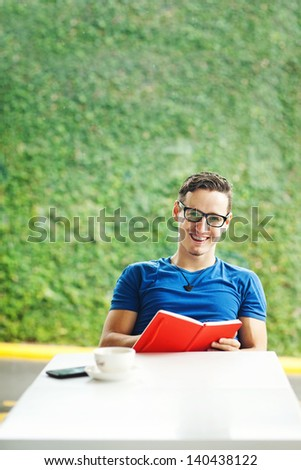 Young man reading a red book at home