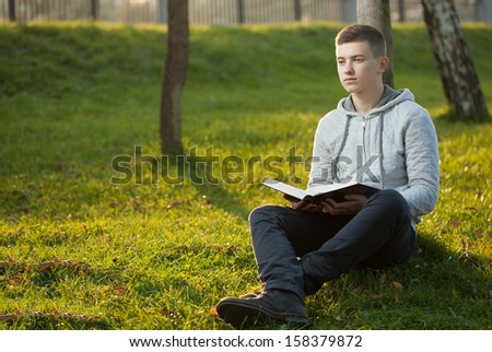 Young man reading Bible in a park