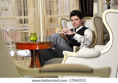 young man reading book and relaxing in luxury indoor - stock photo