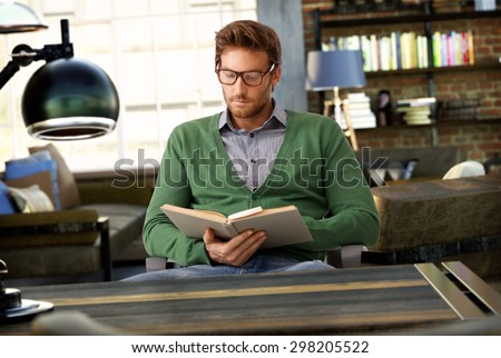 Young man reading book at old-fashioned home. - stock photo