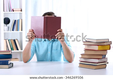 Young man reading book at table in room - stock photo