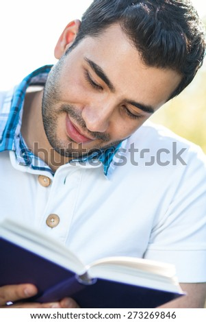 Young man reading book, close up. Outdoors, outside
