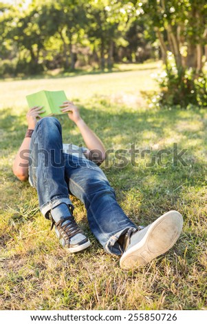 Young man reading book in the park on a summers day - stock photo