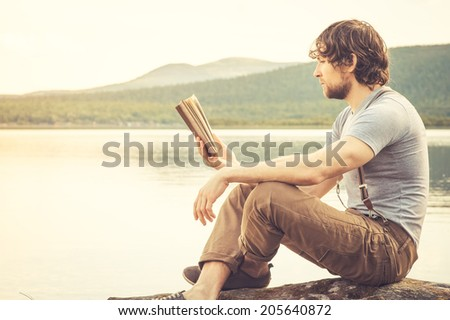 Young Man reading book outdoor with lake on background Summer vacations and Lifestyle concept - stock photo