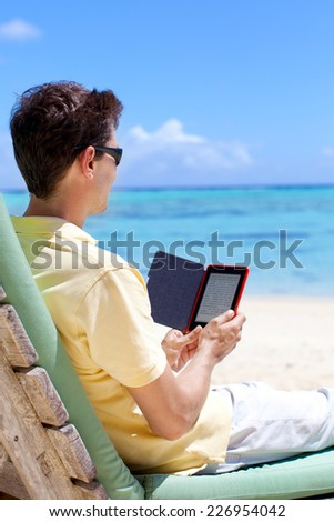 young man reading electronic book at the beach - stock photo