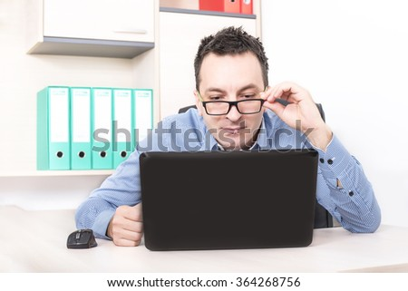 Young man reading emails on laptop in office - stock photo