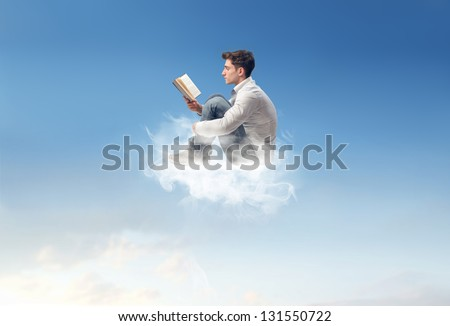 young man reads sitting on a cloud - stock photo
