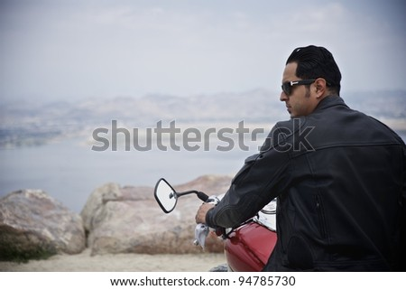 Young man ready to cruise on his motorcycle. - stock photo