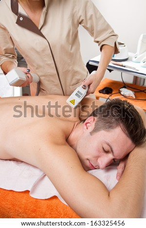 young man receiving laser epilation on beauty center - stock photo