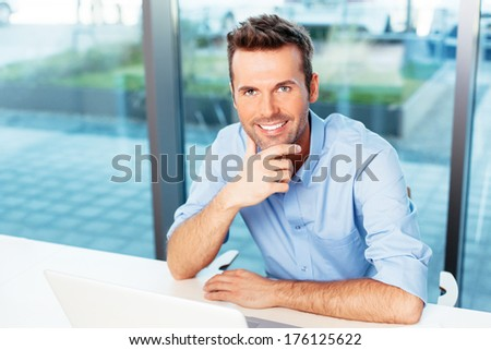 Young man relaxing at a laptop - stock photo